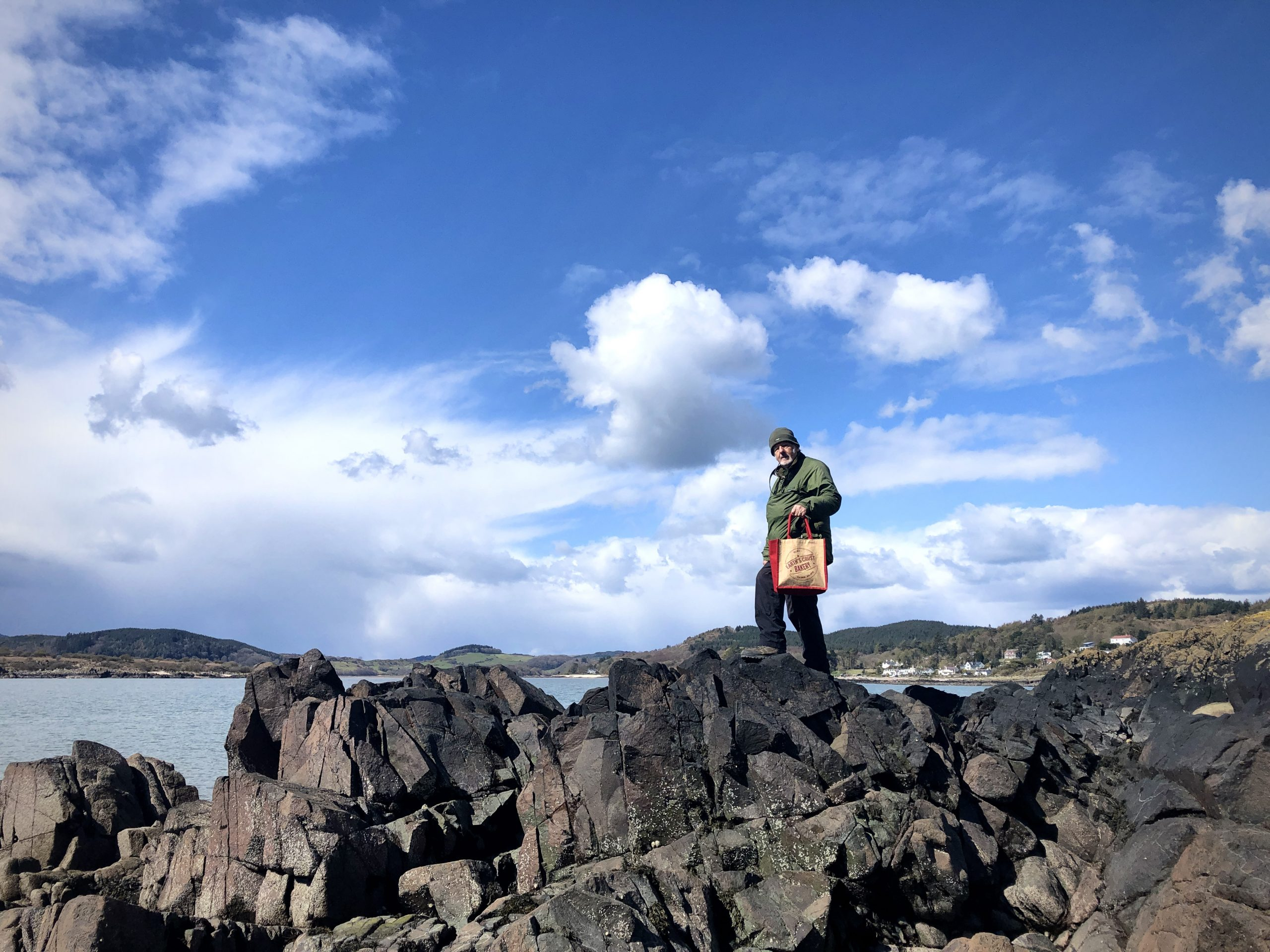 A man standing on the rocks at Rockcliffe with a shopping bag